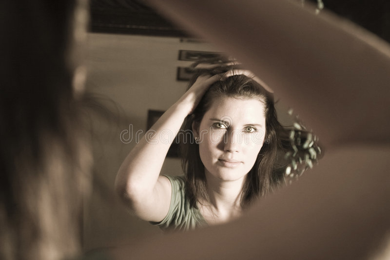Mujer que mira en un espejo imagen de archivo