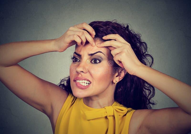 Mujer que mira en un espejo que exprime acné o espinilla en su cara fotografía de archivo libre de regalías