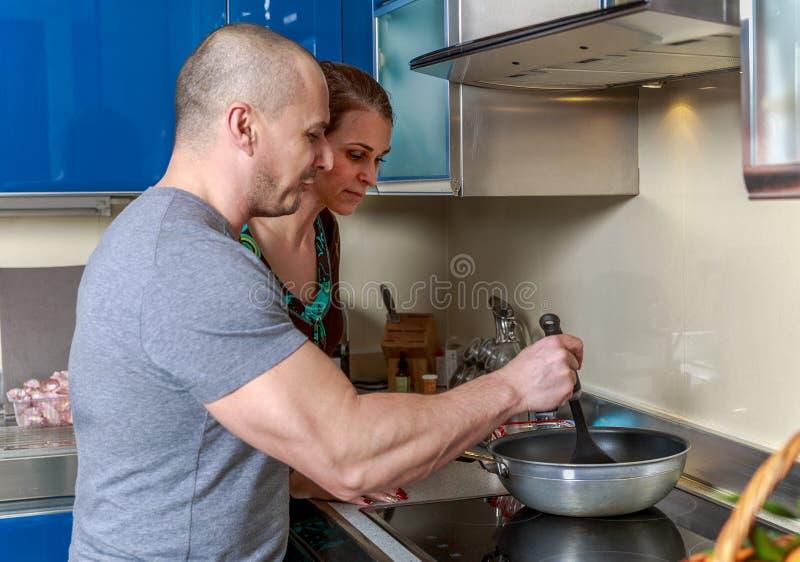 Mujer que mira en una cacerola que su marido se está sosteniendo en una cocina fotos de archivo libres de regalías