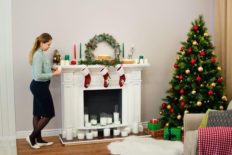 Mujer que mira en una vela en sus manos en casa foto de archivo