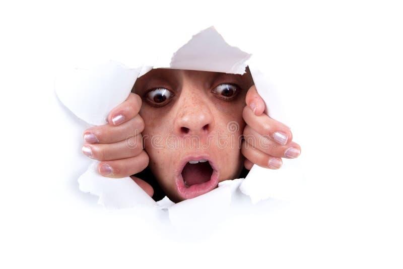 Mujer que mira a escondidas detrás del agujero de la pared imagenes de archivo