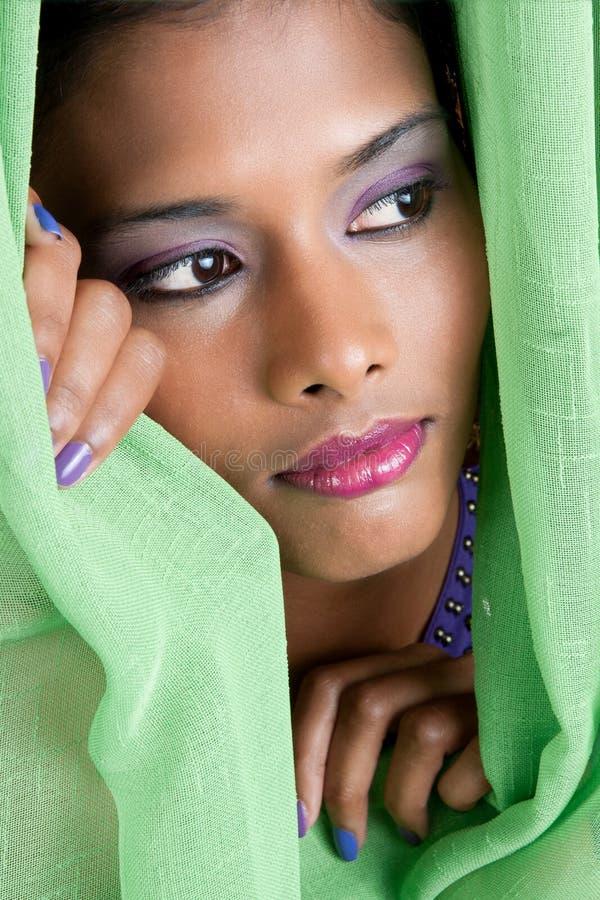 Mujer que mira a escondidas a través de la cortina fotografía de archivo