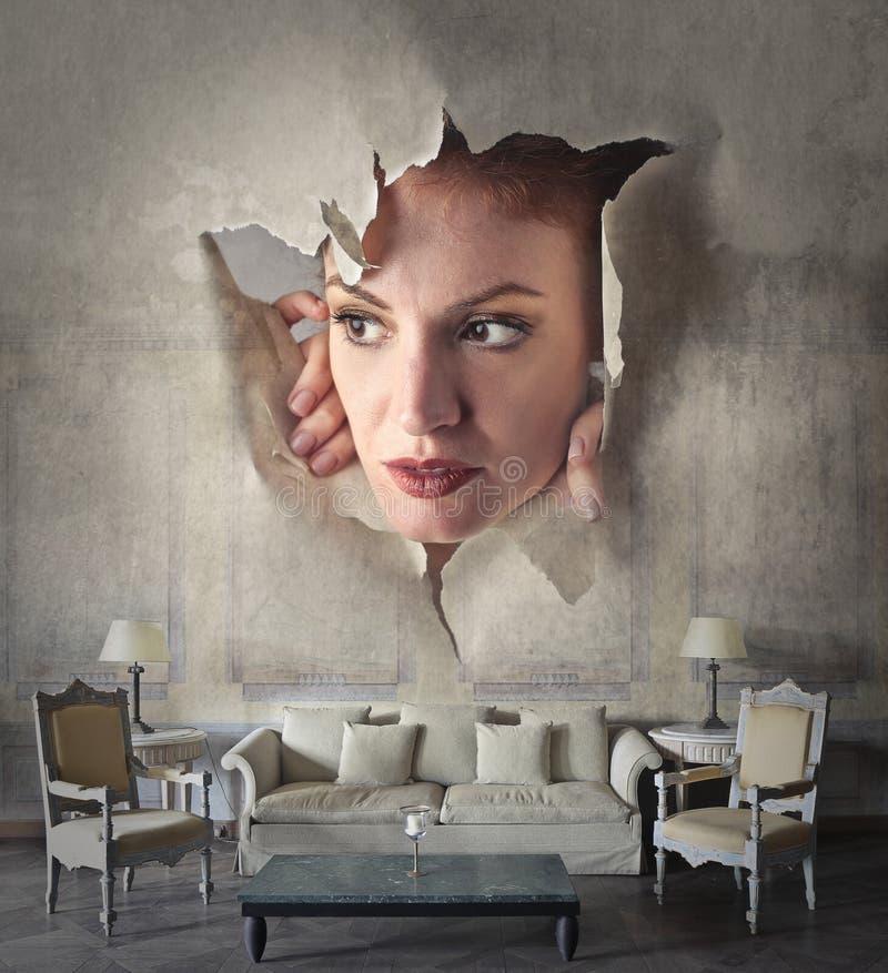 Mujer que mira a escondidas a través de la pared foto de archivo
