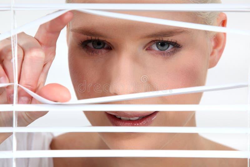 Mujer que mira a escondidas a través de persianas foto de archivo