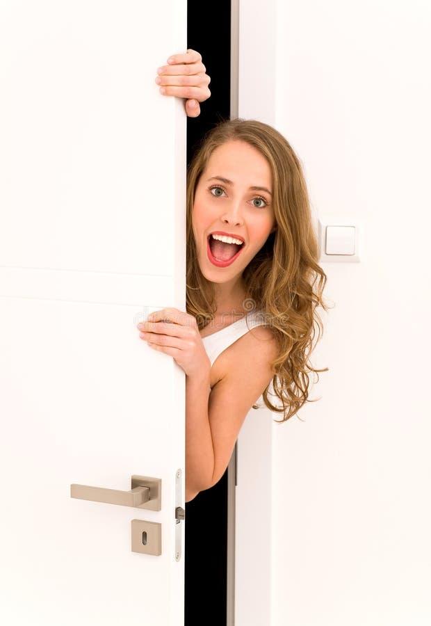 Mujer que mira a escondidas a través de puerta foto de archivo libre de regalías