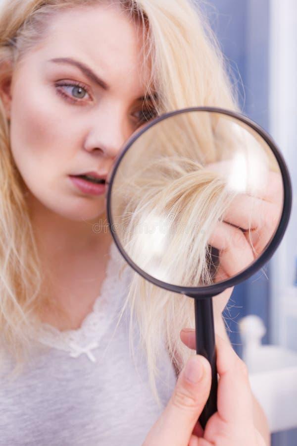 Mujer que mira extremos del pelo a trav?s de la lupa fotografía de archivo