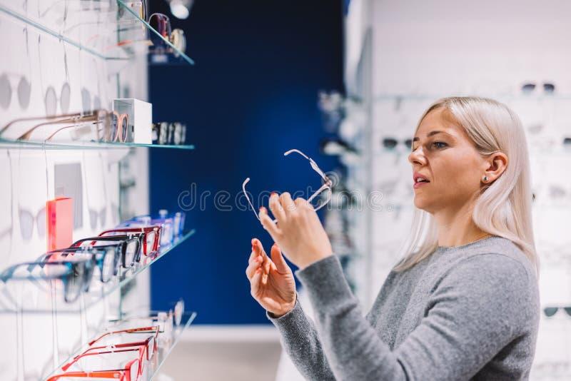 Mujer que mira gafas de la corrección fotografía de archivo