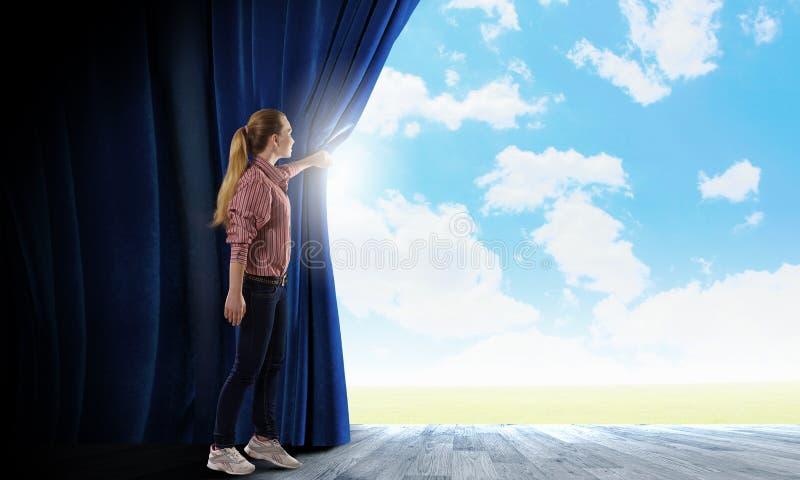 Mujer que mira hacia fuera de la cortina fotos de archivo