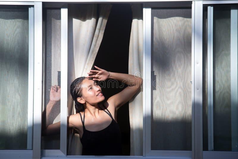 mujer que mira hacia fuera la ventana abierta imagen de archivo