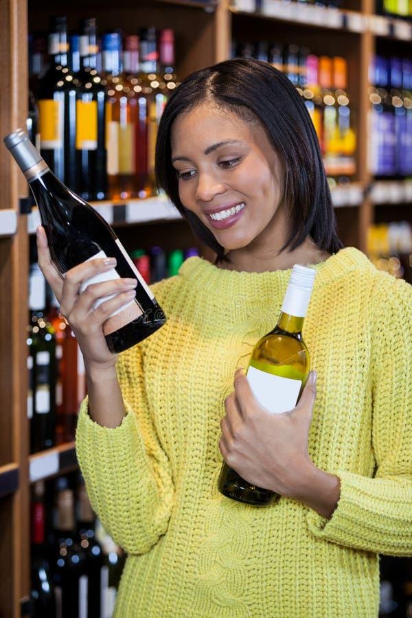 Mujer que mira la botella de vino en la sección del ultramarinos imágenes de archivo libres de regalías