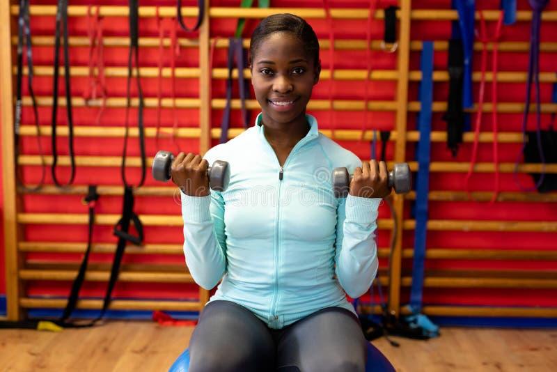 Mujer que mira la cámara mientras que ejercita con pesa de gimnasia en centro de deportes imagen de archivo libre de regalías