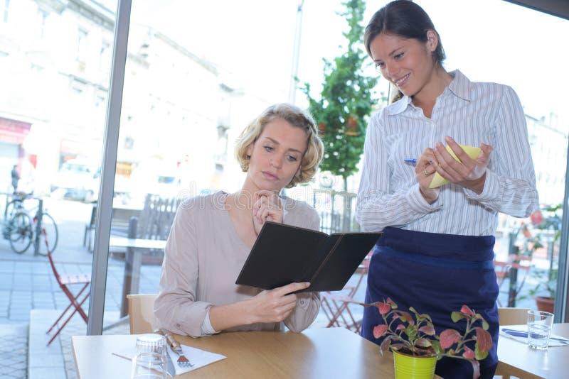 Mujer que mira a la camarera del menú que toma el restaurante de la orden imagenes de archivo