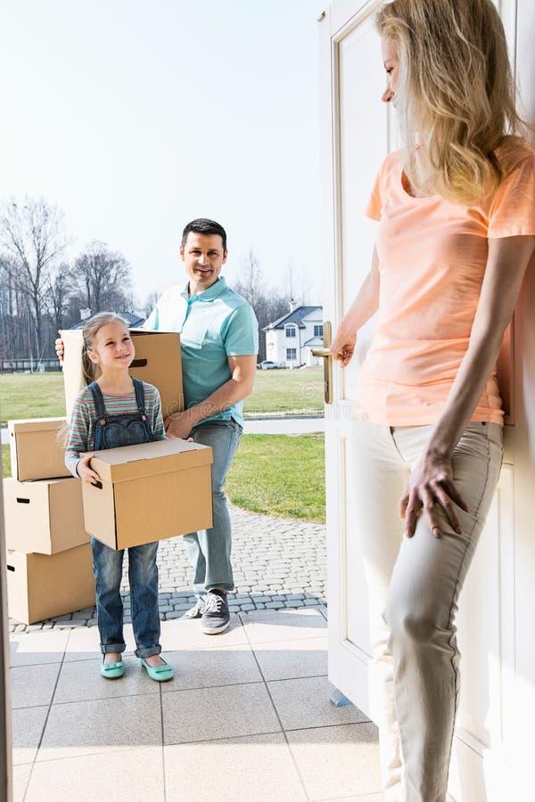 Mujer que mira a la familia con las cajas de cartón que entran en el nuevo hogar imágenes de archivo libres de regalías