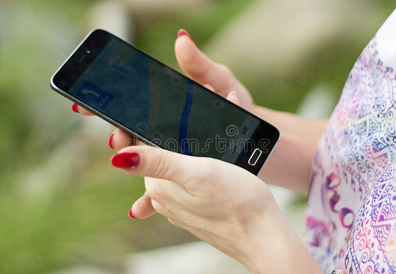 Mujer que mira la mejor manera a la ubicación con el navegador en un teléfono imágenes de archivo libres de regalías