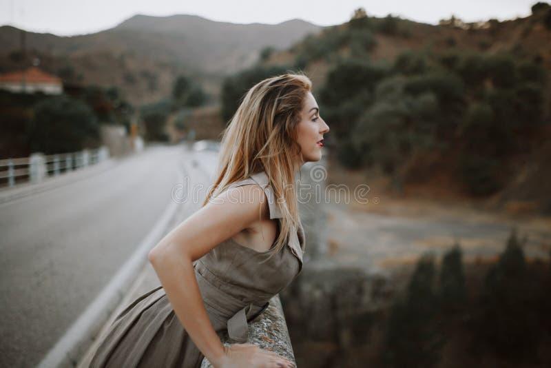 Mujer que mira la naturaleza de un puente foto de archivo