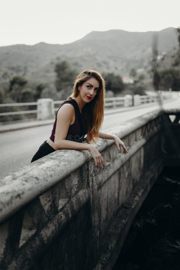 Mujer que mira la naturaleza de un puente imagen de archivo