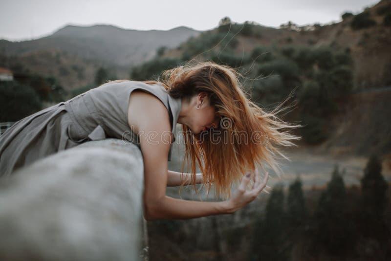 Mujer que mira la naturaleza de un puente mientras que movimientos los brazos con el viento fotografía de archivo