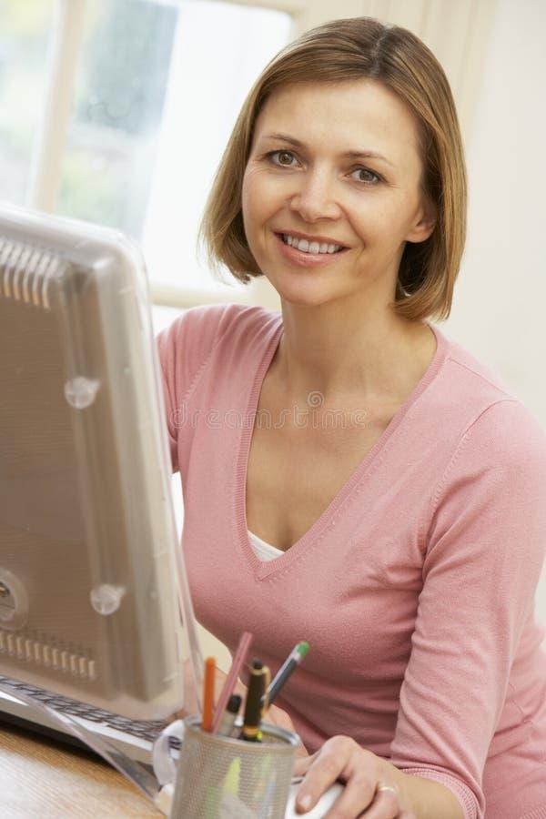 Mujer que mira la pantalla de ordenador imagen de archivo