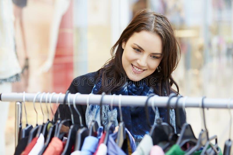 Mujer que mira la ropa en el carril en alameda de compras fotos de archivo libres de regalías