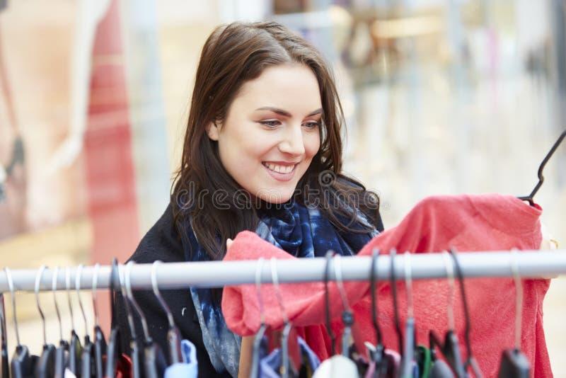 Mujer que mira la ropa en el carril en alameda de compras imagen de archivo