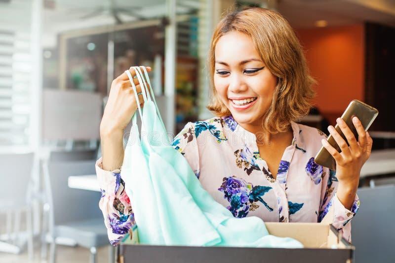 Mujer que mira la ropa que ella consiguió de tienda en línea imagenes de archivo