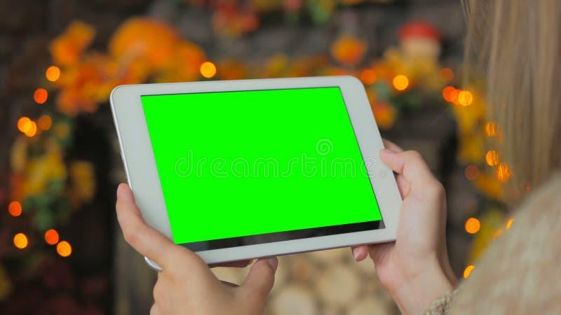 Mujer que mira la tableta con la pantalla verde fotografía de archivo libre de regalías