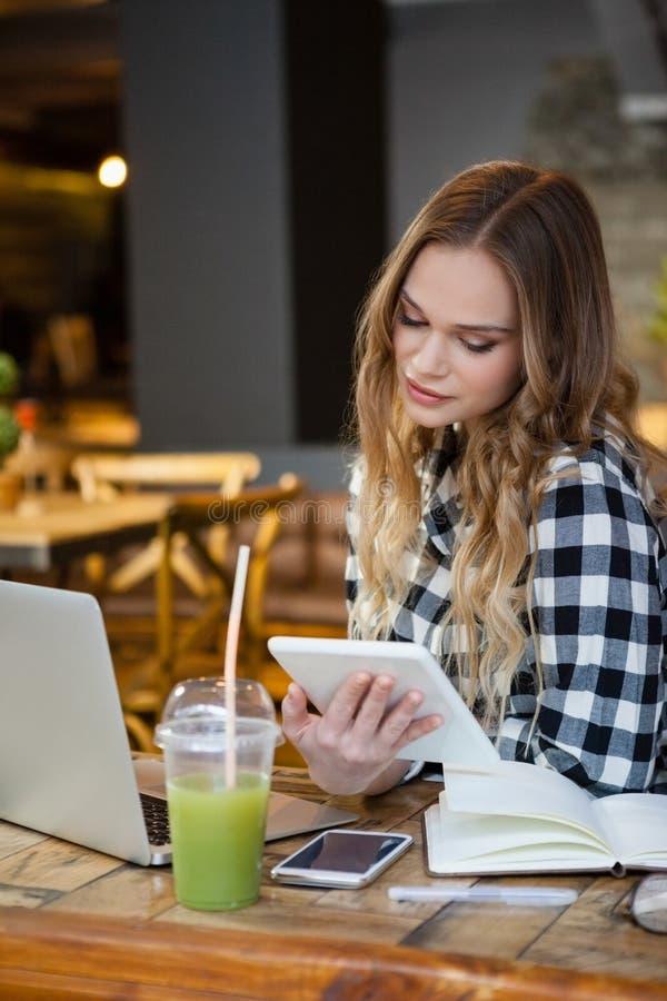 Mujer que mira la tableta mientras que se sienta en la tienda del café imagen de archivo libre de regalías