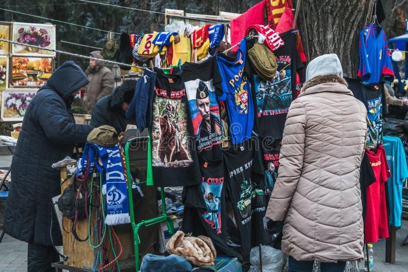 Mujer que mira las camisetas con Vladimir Putin en un pequeño mercado fotografía de archivo libre de regalías
