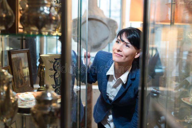 Mujer que mira las decoraciones antiguas en tienda imagen de archivo libre de regalías