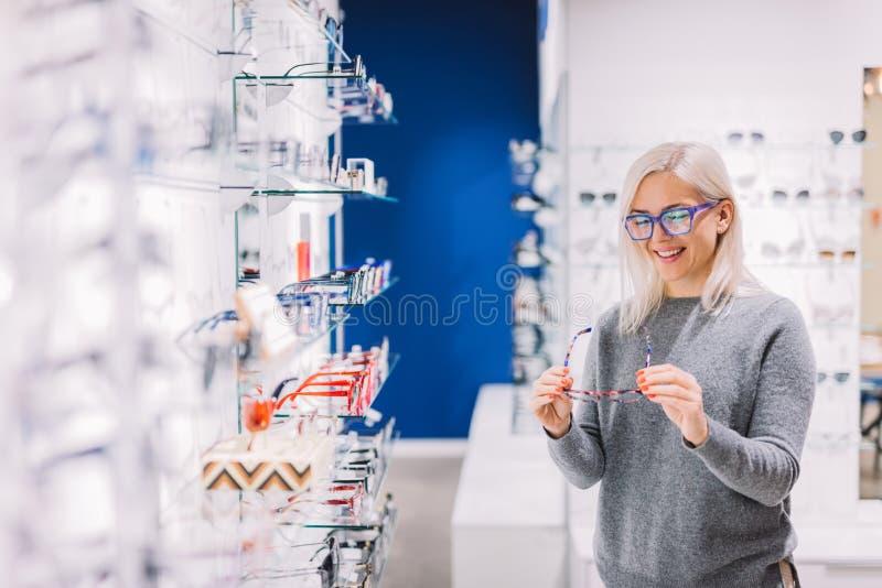Mujer que mira los vidrios la tienda óptica fotos de archivo
