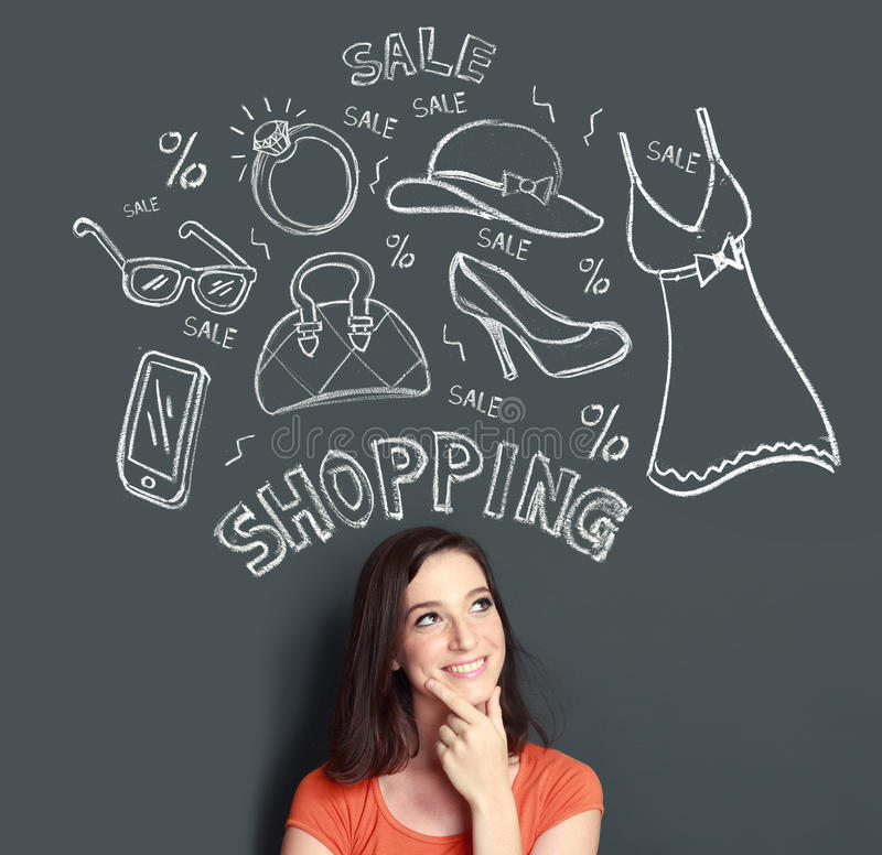 Mujer que mira para arriba de pensamiento en la compra o que hace compras algo fotografía de archivo