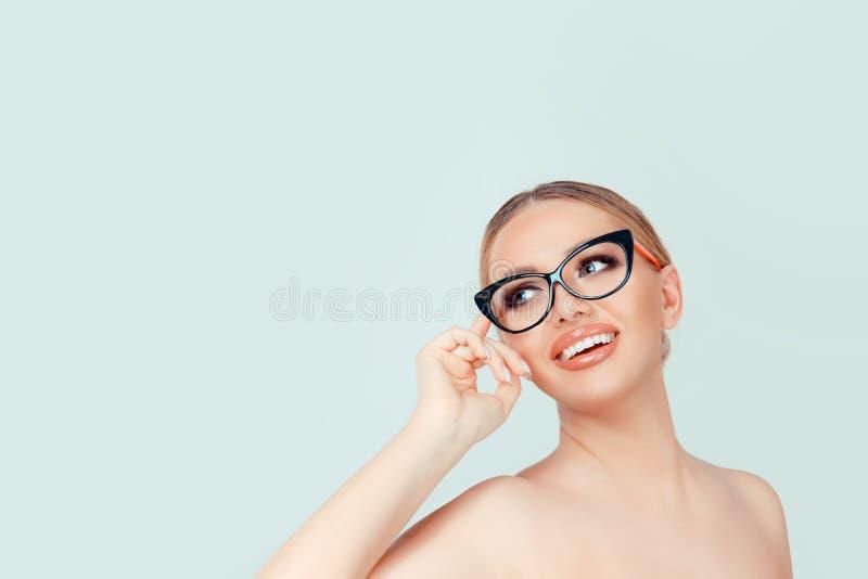 Mujer que mira para arriba a las lentes conmovedoras del lado aisladas en verde claro fotos de archivo libres de regalías