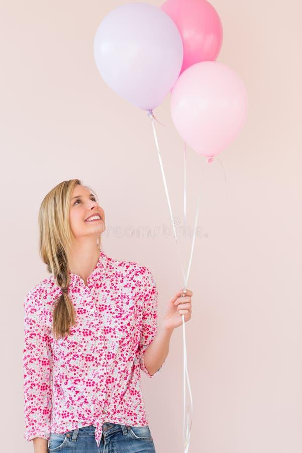 Mujer que mira para arriba los globos contra fondo rosado foto de archivo