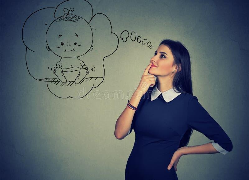 Mujer que mira para arriba y que sueña sobre un bebé imagen de archivo libre de regalías