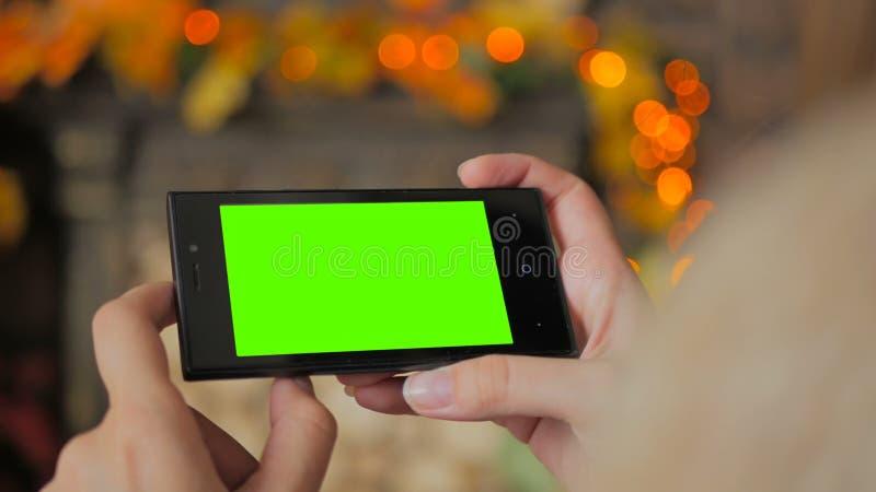 Mujer que mira smartphone con la pantalla verde foto de archivo