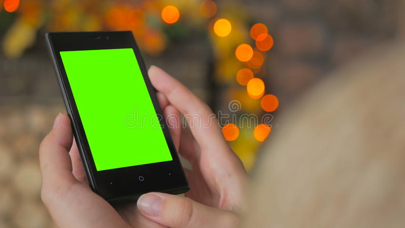 Mujer que mira smartphone con la pantalla verde fotos de archivo