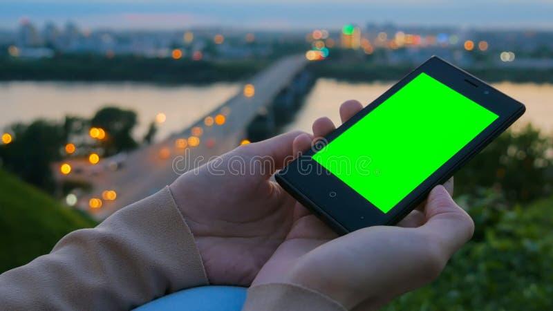 Mujer que mira smartphone con la pantalla verde imágenes de archivo libres de regalías