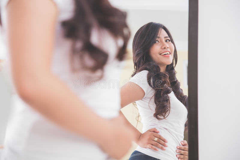 Mujer que mira su imagen en el espejo fotografía de archivo