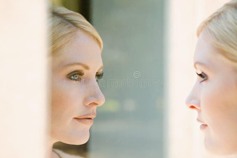 Mujer que mira su reflexión fotos de archivo