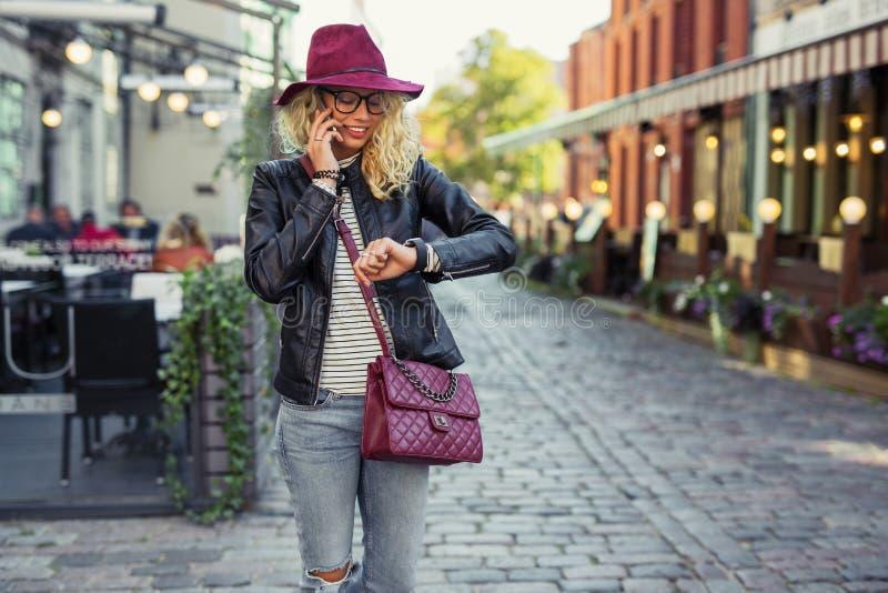 Mujer que mira su smartwatch y que habla en el teléfono móvil fotos de archivo