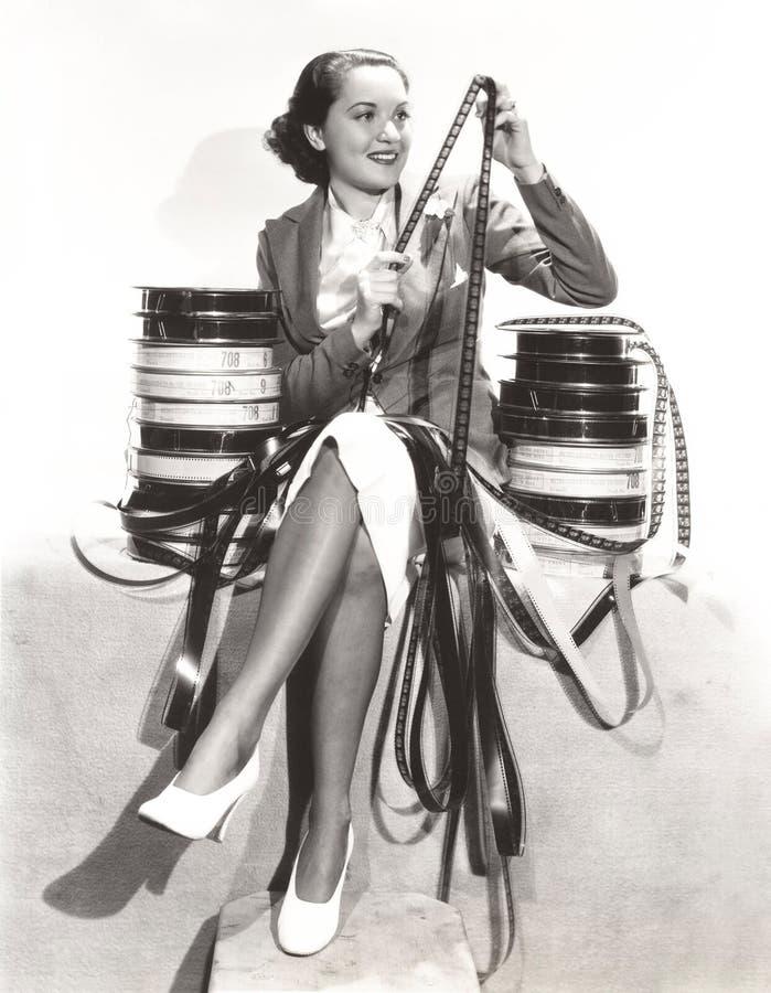Mujer que mira tiras de película imagen de archivo libre de regalías