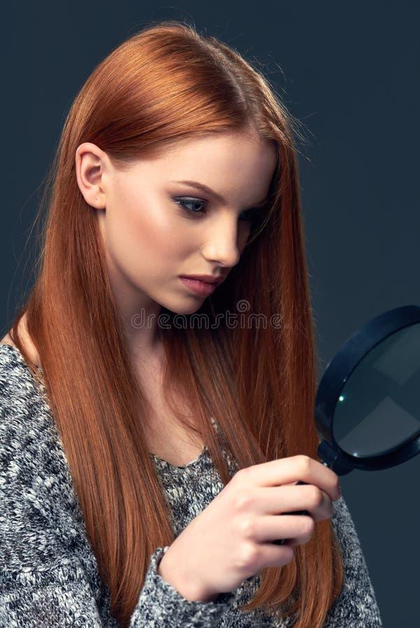 Mujer que mira a través de la lupa foto de archivo libre de regalías