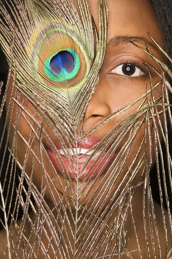 Mujer que mira a través de pluma. imagen de archivo