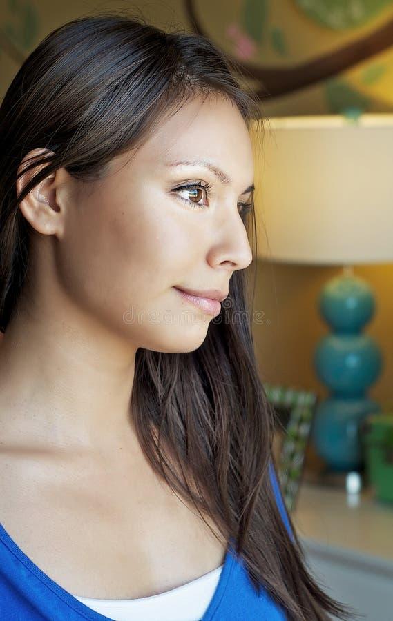 Mujer que mira a través de ventana imagen de archivo