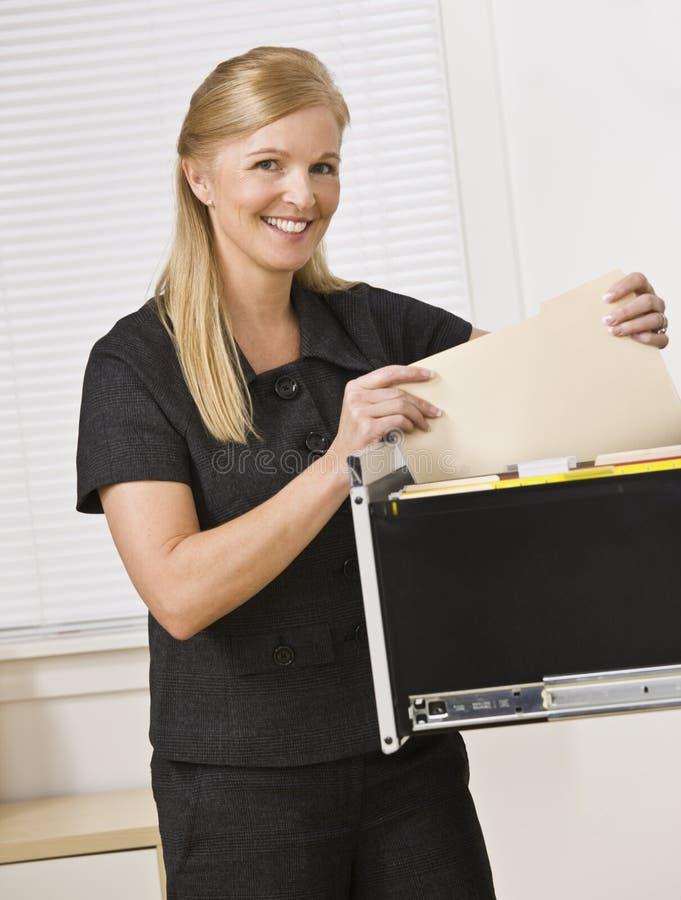 Mujer que mira a través del cabinete de archivo fotografía de archivo libre de regalías