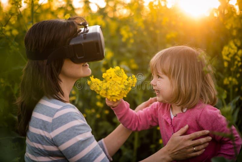 Mujer que mira a través del dispositivo de VR y que juega con su hija imagenes de archivo
