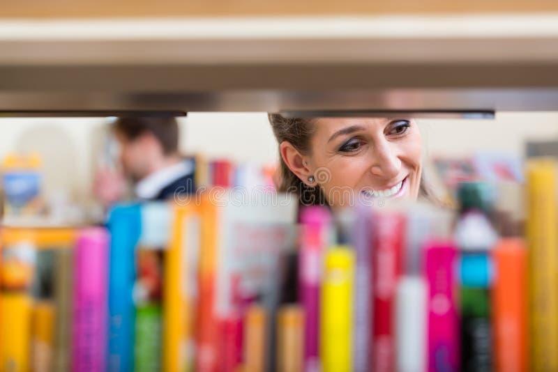 Mujer que mira a través del estante de los libros que eligen el volumen para leer fotografía de archivo libre de regalías