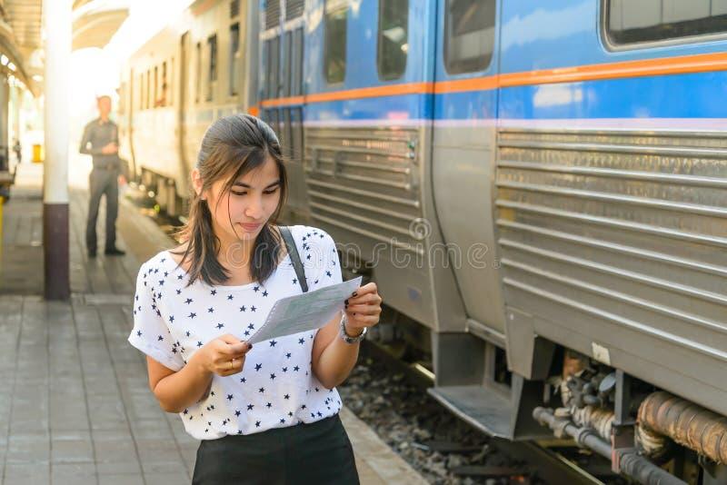 Mujer que mira un boleto antes de subir el tren en la plataforma imagen de archivo