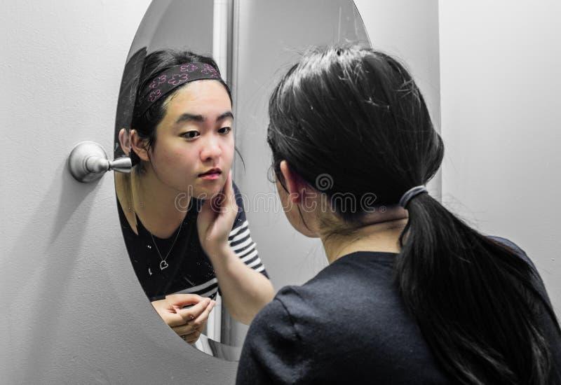 Mujer que mira un espejo fotos de archivo