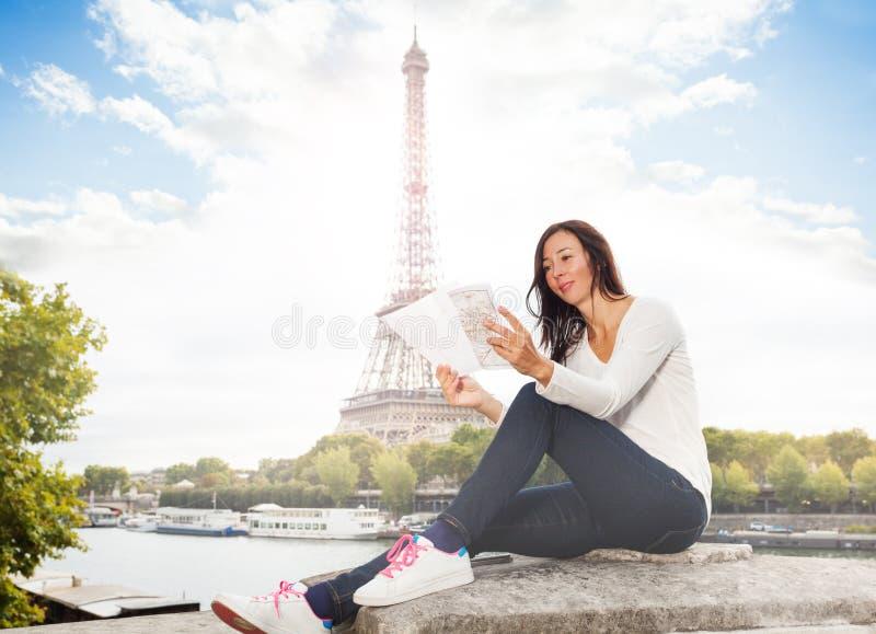 Mujer que mira un mapa contra la torre Eiffel fotografía de archivo libre de regalías